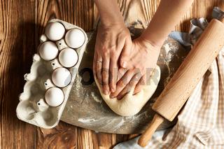 Female hands kneading dough