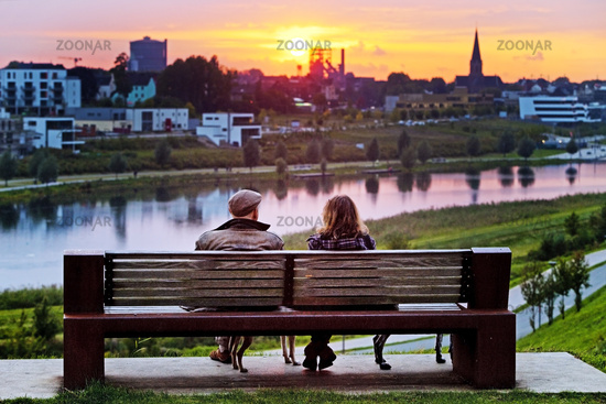 Two people on a bench and two dogs at the Phoenix lake at sunset, Dortmund, Ruhr area, Germany