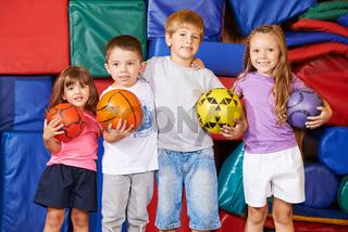 Gruppe Kinder mit Bällen in der Turnhalle