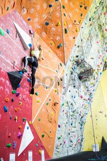 Fit blonde rock climbing indoors
