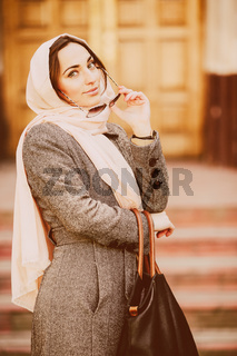girl in a coat posing on building background