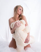 Image of sensual nude woman hugging teddy bear