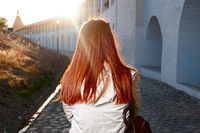 Rear view of red haired woman walking in the street near old fortress in europe backlit with sunflares