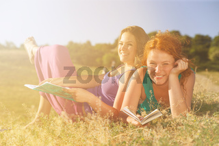 Two women read on grass