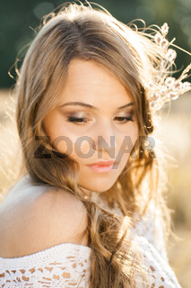 Close up portrait of a beautiful lady model in open field at sunset