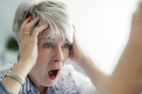 An elderly lady looks in horror in the mirror and tearing her hair.