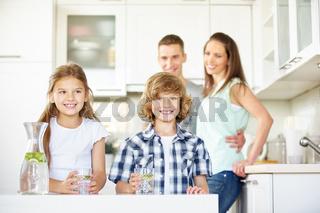Kinder in der Küche mit Karaffe mit frischem Wasser