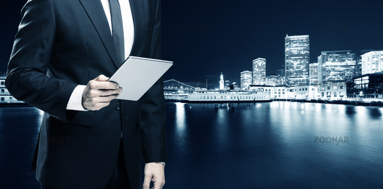 businessman with tablet with modern buildings near water in san francisco