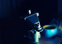 Small DIY hobby clamp with detail in dark room, backlit, toned image