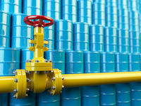 Yellow gas pipe line valves and blue oil barrels. Fuel and energy industrial concept.