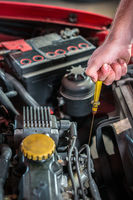 Car mechanic in auto repair service checking oil
