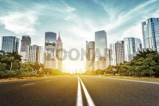 asphalt road and skyscrapers under sunbeam