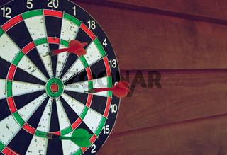 Darts over wooden background. Arrows missed target
