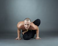 Yogi performs asana. Studio shot, on gray backdrop