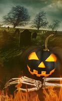 Black pumpkin with skeleton hand with graveyard in