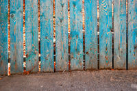 Old fence bottom painted in blue color