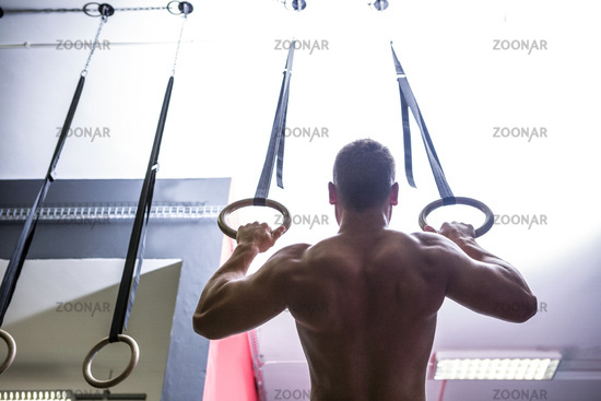 Back view of muscular man doing ring gymnastics