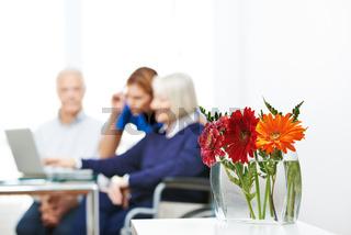 Blumen in Vase mit Senioren am Computer