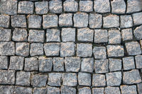Old road paved with granite stone cubes