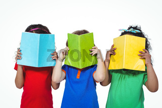 Three kids standing with books in front of their faces