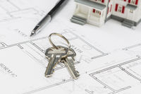 Model Home, Engineer Pencil and Keys Resting on House Plans