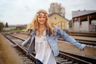Junge Frau im Hippie-Look steht auf Schienen