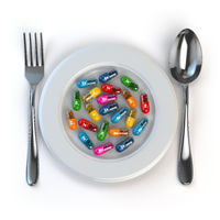 Diet. Pills or vitamins on plate with spoon and fork.