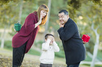 Mixed Race Parents With Gifts for Young Boy Hiding Eyes