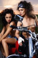 Two sexy naked girls sitting on a motorcycle outdoors