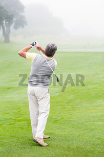 Golfer swinging his club on the course
