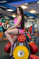 Image of sporty girl sitting on rack for rod discs
