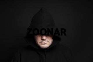 man wearing black hoodie hiding eyes
