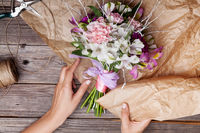 Packing a rustic bouquet from gillyflowers and alstroemeria on old wooden background with wooden heart and scissors with paper