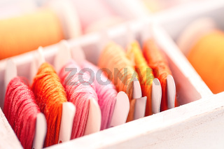 Collection of yellow, red, pink  threads  arranged in a white wooden box