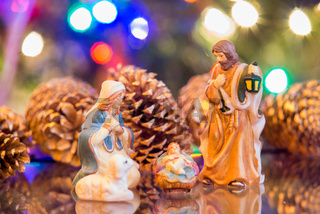 nativity set with mary joseph and jesus with christmas lights background