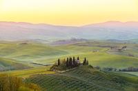 Farmhouse in a tuscany landscape before sunrise