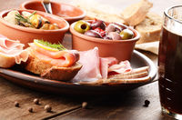 Tapas of salmon, mussels, jamon and olives with beer