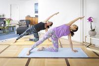 two women doing yoga at home Vasisthasana pose