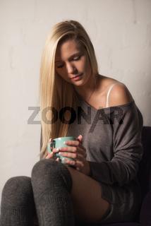 sinnliches blondes mädchen sitzt auf einem sessel und hält einen kaffeebecher