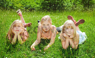 girls lying on green grass