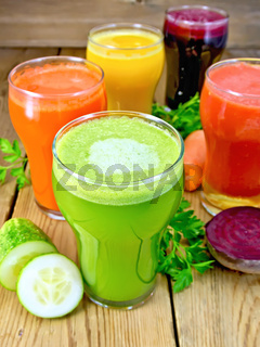 Juice cucumber and vegetable in glassful on board