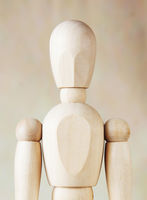 Wooden dummy against brown background