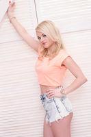 glamorous blonde woman wearing shorts and top
