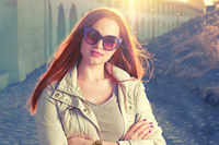 Beautiful young red-haired woman with long hair, beautiful makeup with bright pink lips, wearing a light coat and funny  sunglasses backlit