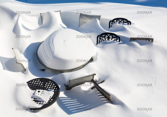 Outdoors garden table and chairs buried in snow drift