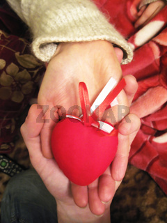 Valentine red heart in woman and man hands