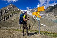 Wanderer betrachtet Wegweiser auf dem Griespass
