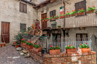 Courtyard, house and balcony with flowers.