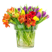 Flower bouquet from colorful tulips in glass vase isolated.
