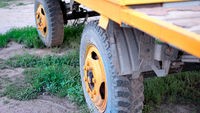 The old truck tire painted in bright yellow color in rural area closeup, selective focus